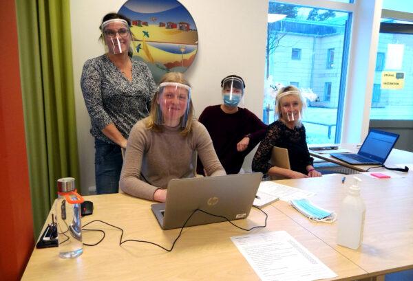 Foto på Malin Söderdahl (intern service), Hanna Axelsson (Väggabadet), Ingegerd Åberg (verksamhetsutvecklare Omsorgen) och Susanne Håkansson (HR) vid ett bord i full skyddsutrustning.