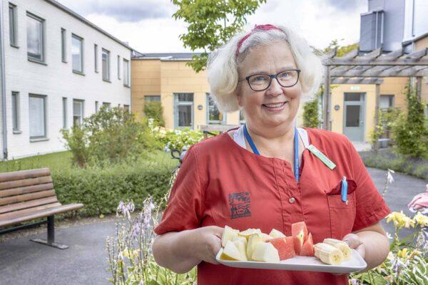 Foto på Marita Martinsson, kvalitetsundersköterska, har förberett en bricka med frukt att servera de boende på Östralycke äldreboende.