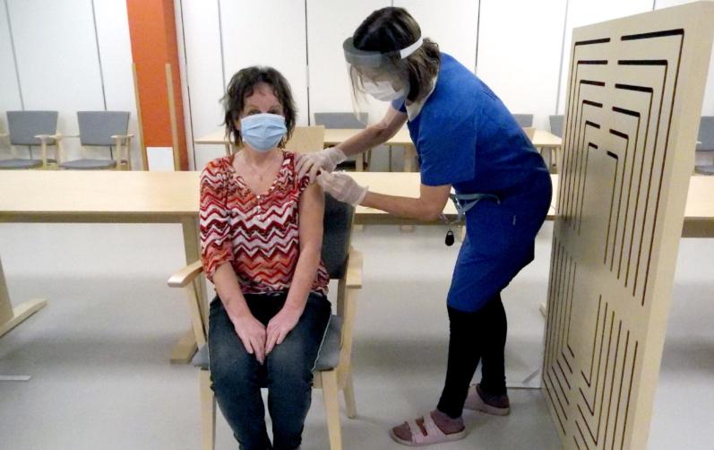 Foto på när sjuksköterskan Marina Torstensson får sin första vaccindos av Margareta Pålsson.