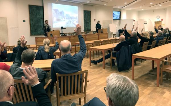 Foto på folk i Rådhussalen som lyssnar på arkitekternas presentation.