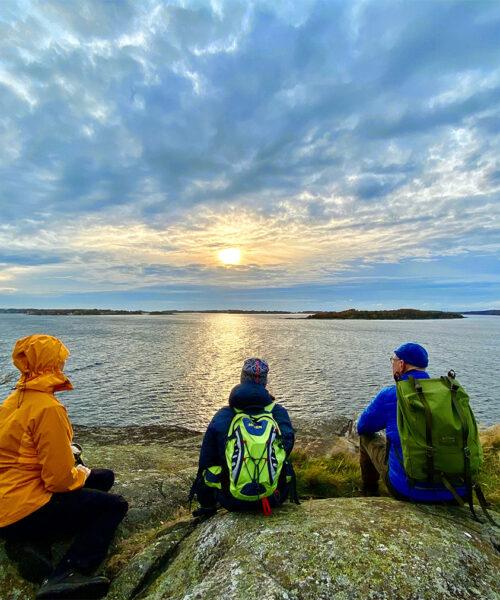 Tre personer sitter på klippa och tittar ut över havet