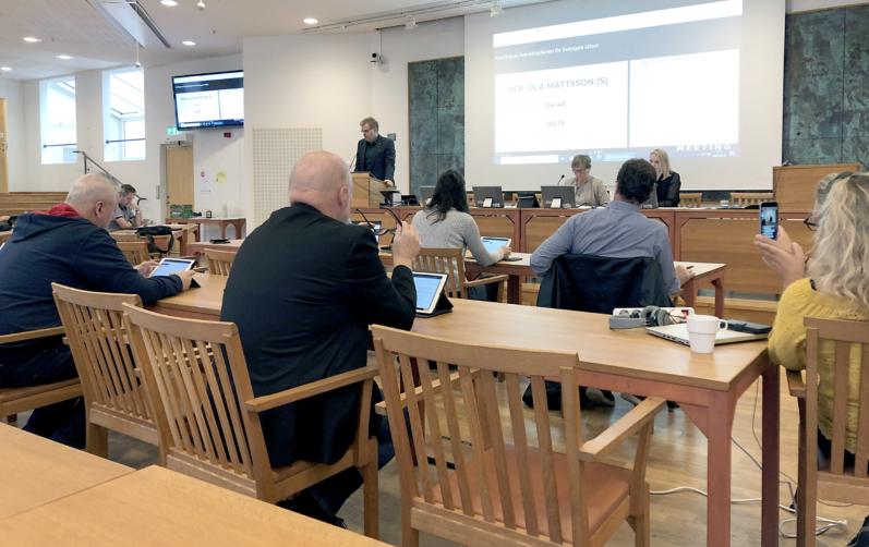 Förtroendevald sitter i Rådhussalen i Karlshamn under kommunfullmäktiges sammanträde den 28 september.