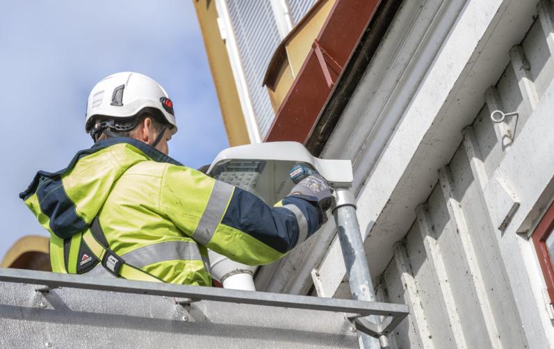 En man sitter i en skylift och monterar en led-lampa.