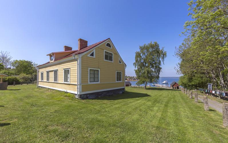 Den gula lärarbostaden på Tärnö med utsikt över havet.
