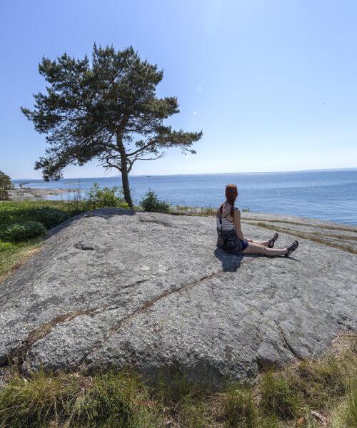 Tjej som sitter på klippa i Sternö