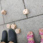 Foto på barnfötter och stora speltärningar i trä på stenblock.