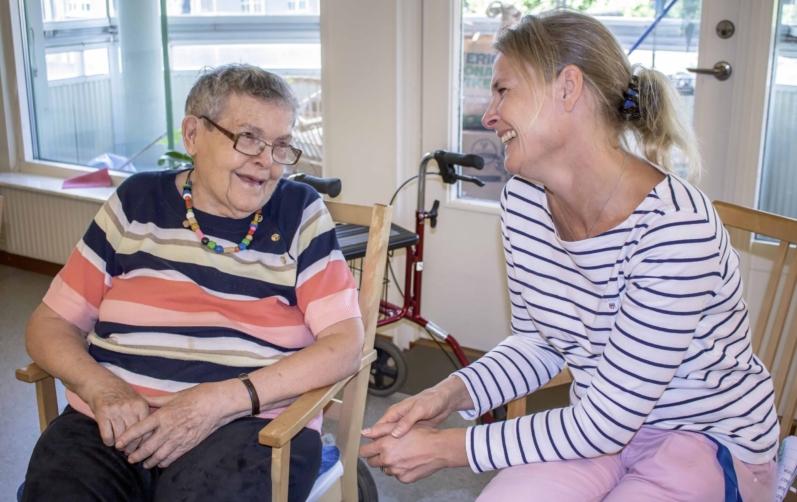 Foto på en äldre kvinna som sitter och pratar med en lite yngre kvinna på ett boende.