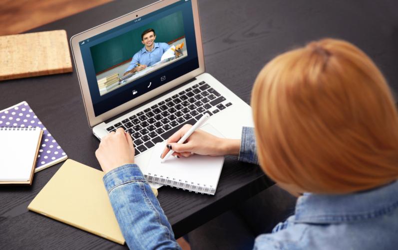 Fotot föreställer en rödhårig flicka som man ser bakifrån som sitter och antecknar i ett block framför fatorn där man ser en person som pratar.