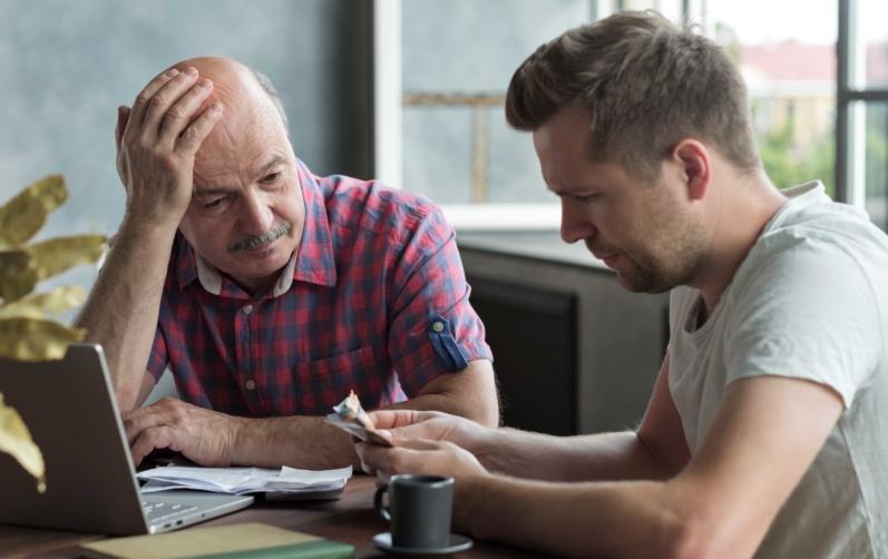 Foto på en äldre man som ser bekymrad ut och en yngre som sitter och räknar pengar.