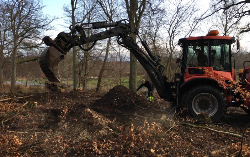 Foto på grävmaskin som schaktar bort jord.