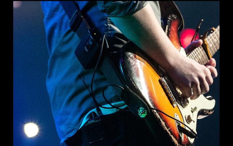 Foto på en hand som spelar elgitarr