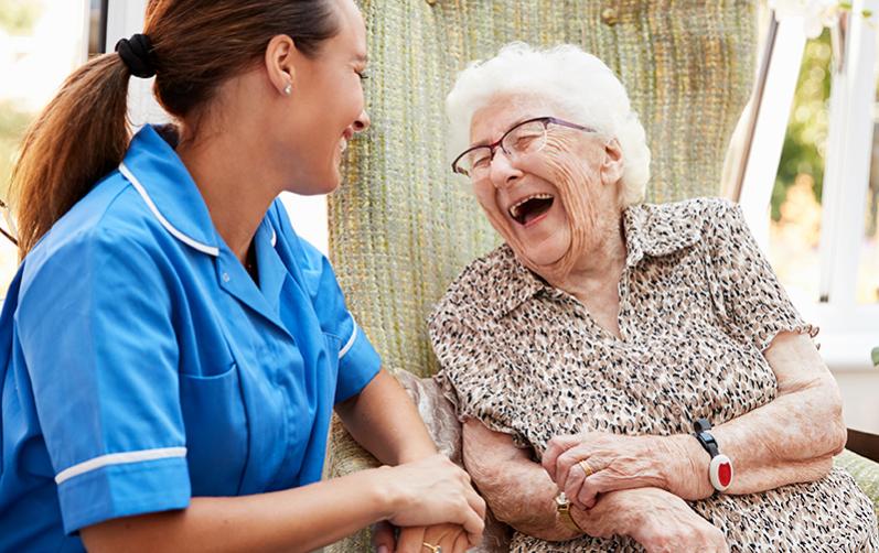 Foto på en ung kvinna i blå rock som sitter och skrattar med en äldre kvinna