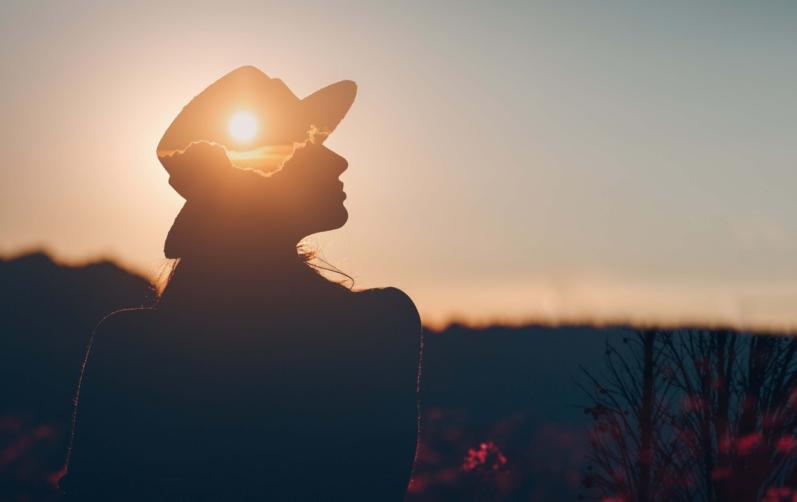 Foto på en kvinna med hatts siluett i solnedgång med solen i hatten.