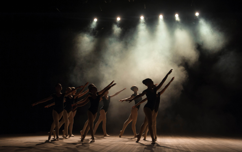 En grupp dansar balett på en scen i strålkastarljus.