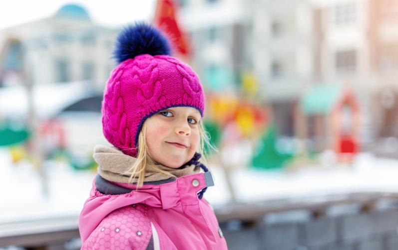 Foto på en liten flicka i rosa jacka och mössa utomhus.