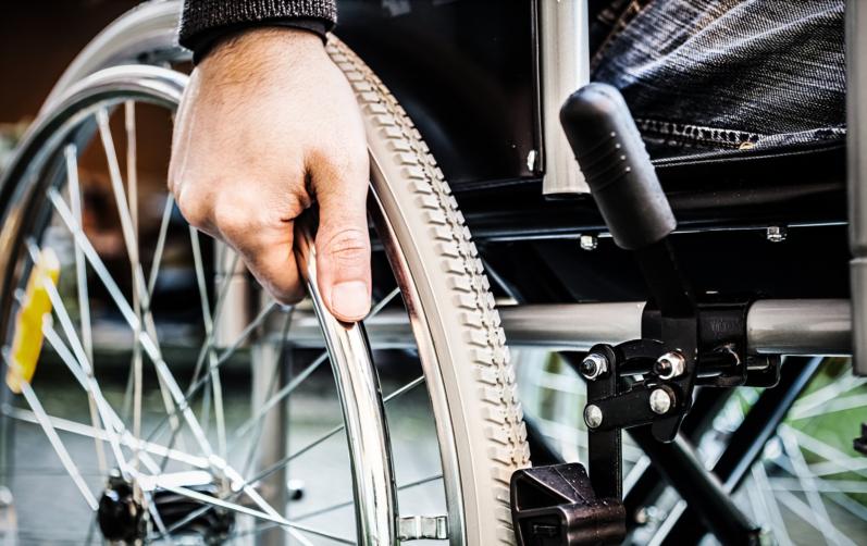 Närbild på en hand som håller i ett hjul på en rullstol.