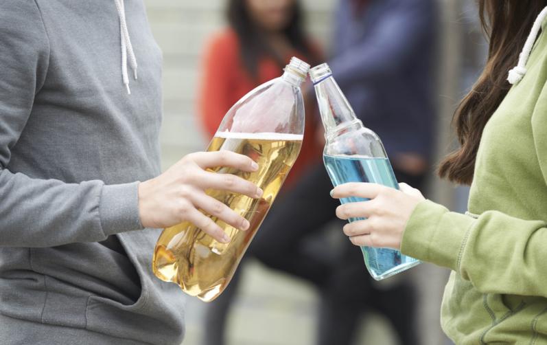 Foto på en tjej som skålar med en flaska med blått innehåll med en kille som skålar i en pet-flaska med gult innehåll.