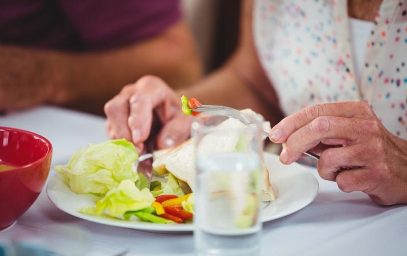 Foto på en äldre dams hand som äter sallad på en tallrik