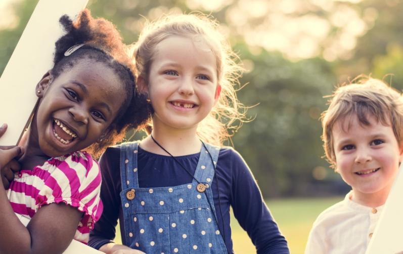 Tre glada barn utomhus.