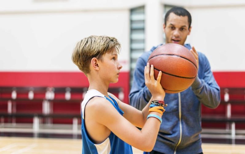 Foto på en ung kille som ska kasta en basketboll med sin coachande tränare bredvid.