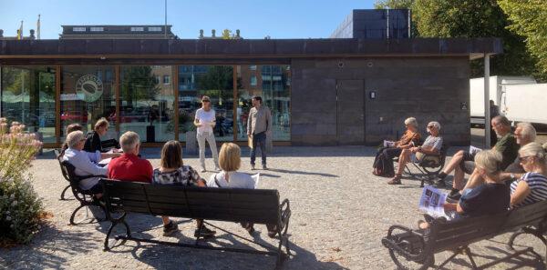 Två personer står framför torgbyggnaden och pratar inför en samling människor.