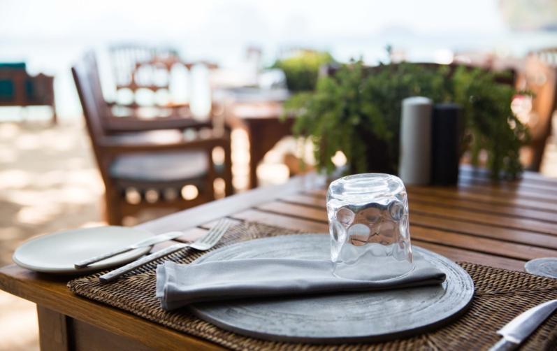 Foto på en dukning med bestick och glas på ett träbord utomhus